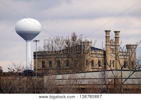 A view through trees of the old Illinois State Penitentiary, and a white water tower, in Joliet, Illinois, during the autumn.