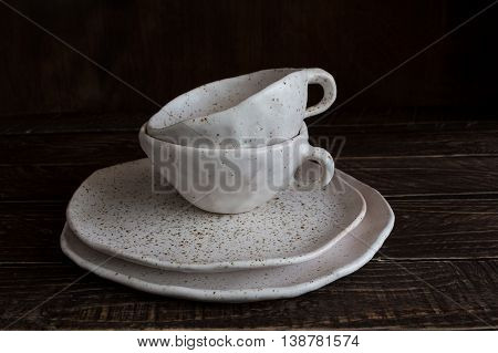 set of white pottery on a brown background white pottery in brown speckled plates and cups from clay.