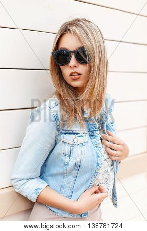 Sexy Beautiful Stylish Girl In Sunglasses And A Blue Jeans Jacket Standing Near The Wooden Wall