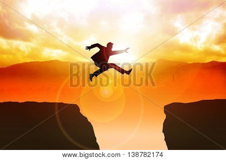 Man jumping over the ravine on dramatic background
