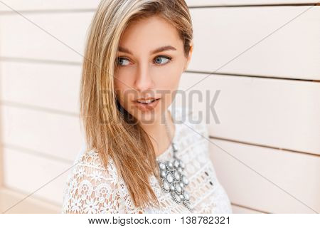 Close-up Portrait Of A Beautiful Woman In Stylish Vintage White Lace Blouse Looks To The Side On A B