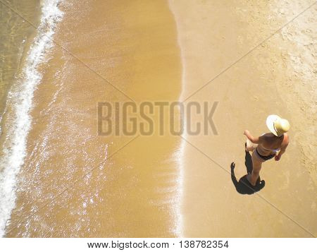 woman with hat walking along the seashore at noon