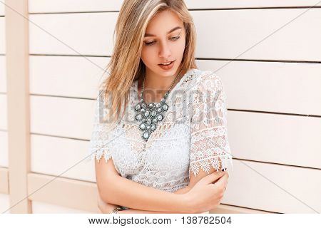Beautiful Young Girl In White Lacy Blouse Looking Down Near A Wooden Wall