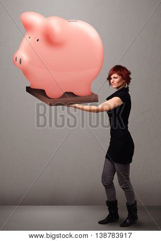 Beautiful young girl holding a huge savings piggy bank