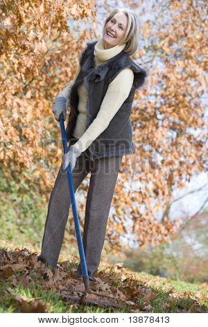 Senior woman tidying autumn leaves from garden
