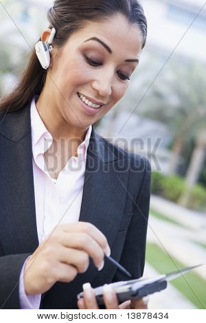 Businesswoman using earpiece and PDA outside
