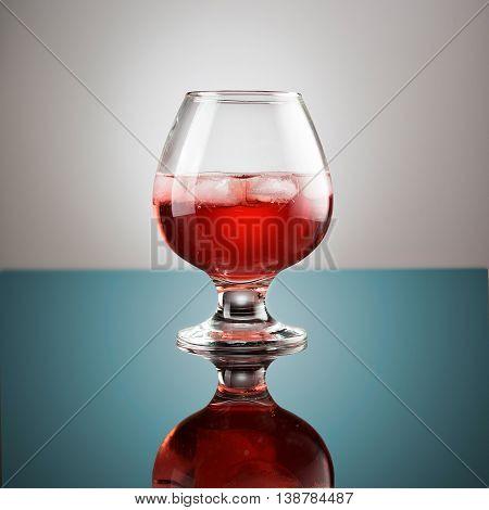 Beer in a glass on glossy surface with drops isolated