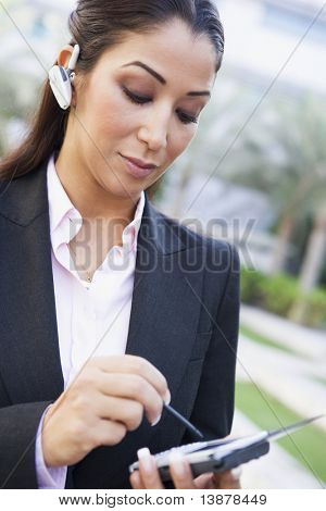 Businesswoman using PDA and earpiece outside