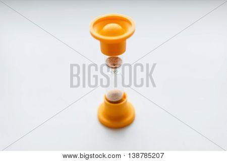 Vintage orange plastic hourglass on a white background.