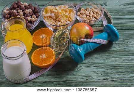 The concept of a healthy lifestyle. Cereals and fruit - diet and breakfast. Cornflakes orange juice yogurt nuts honey tangerines apple dumbbell and measuring tape on rustic wooden table.