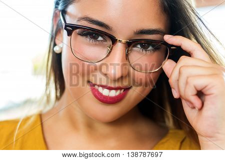 Close up stylish portrait of attractive young woman wearing eye wear. Girl with smooth skin and seductive smile.