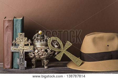 Archeological and adventure concept for lost artifacts with hat, vintage books, iron vase, key of life, vintage cross on brown background