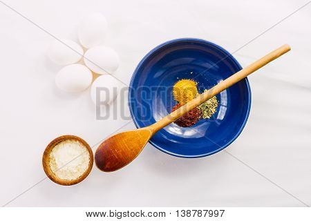 Blue bowl with paprika curry and oregano wooden spoon eggs and dehydrated potato on white tablecloth