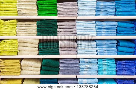 Big pile of colorful towels at shelf