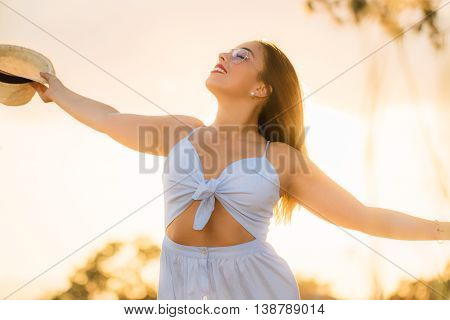 Close up backlit portrait of young woman standing with arms open outdoors at sunset.