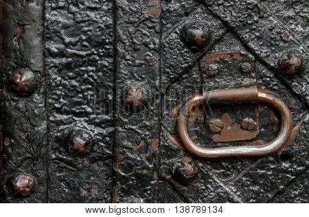Detail of wrought iron door with a metal handle. bound plates and curly old nails