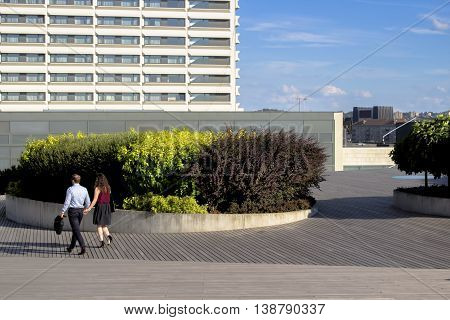 VILNIUS, LITHUANIA - JUNE 29, 2016. An unidentified couple walk in Vilnius Swedbank Terrace - a modern terrace which is part of the office complex near Neris river