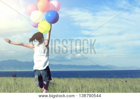 cheering young asian woman running on sunset grassland with colored balloons