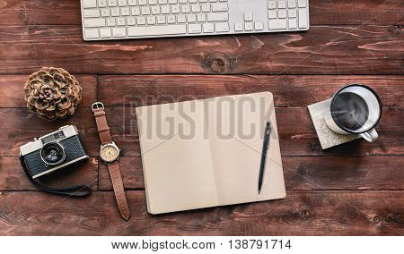 Work space on wood table of a creative designer or photographer with laptop sketchbook coffee and other objects of inspiration. Stylish home studio concept of technology trends. Vintage filter look