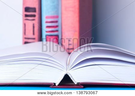 Open Book, Stack Of Colorful Hardback Books On Light Table. Back To School. Copy Space For Text