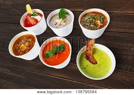Variety of restaurant hot dishes, healthy food. Japanese miso soup, asian fish soup, russian borscht, english pea soup with bacon, mushroom soup, spanish gazpacho at brown rustic wood