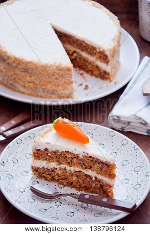 Homemade Carrot Cake with pecans, butter cream on a white plate