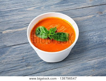 Spanish cuisine hot food delivery - tomato diet cream soup gazpacho at blue wood background in white plastic plate