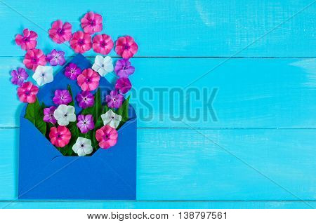 Blue cover of letter with flowers - love message on blue wooden table. Top view. Empty space for text.