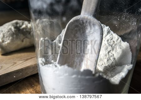 Big Glass Flour jar with a wooden spoon inside close up