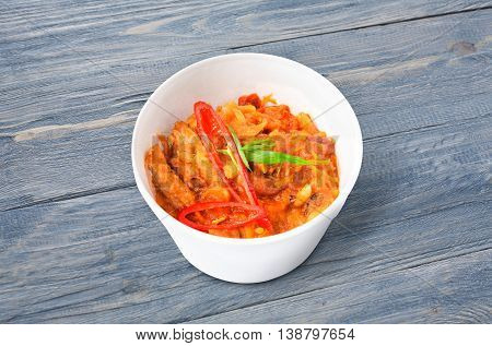 Mexican cuisine food delivery - chili con carne in white plastic plate closeup at rustic blue wood background