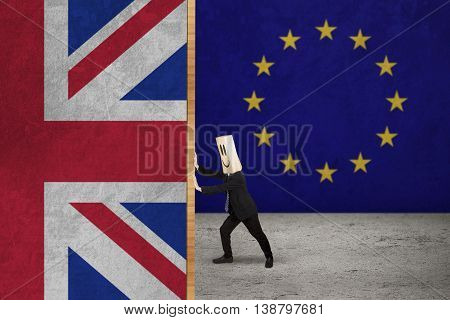 Brexit concept. Businessperson with cardboard head pushing flag of England with EU flag background