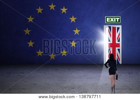 Brexit concept. Young businesswoman looking at exit door with flag of European Union and United Kingdom