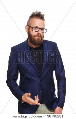 Young bearded man wearing glasses isolated at white background. Portrait of a confident stylish guy in eyeglasses looking at camera. Boy style, trendy hipster with cool hairstyle in blue suit.