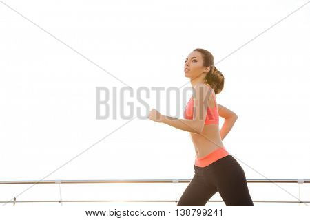 Pretty young woman athlete running outdoors in the morning