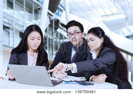 Young businesswoman pointing on the laptop to show document at her partners