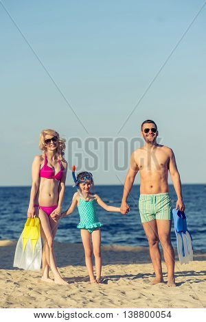 Portrait of young parents and their little daughter in swimsuits and sun glasses looking at camera and smiling standing on the sunny beach. Couple is holding swim fins