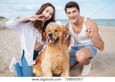 Young stylish beautiful couple in love sitting playing with dog showing v sign