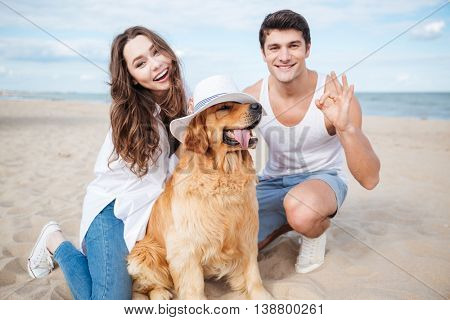 Young stylish beautiful couple in love sitting playing with dog showing okay gesture