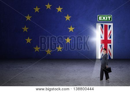 Brexit concept. Female worker standing in front of exit door with flag of England and EU