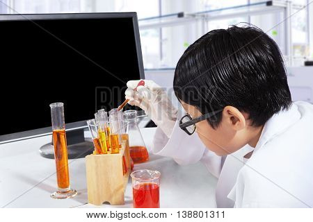 Little boy studying as a scientist while doing experiments with chemical in the laboratory