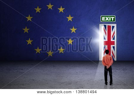 Brexit concept. Businessman looking at exit door with flag of United Kingdom and European Union