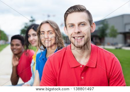 Laughing caucasian young adult and multiethnic friends outdoor in the summer