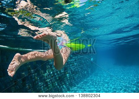 Funny underwater photo of baby girl swimming with fun on yellow ring in clear blue aqua park pool. Healthy family lifestyle children water sports activity and fitness with parents on summer vacation.