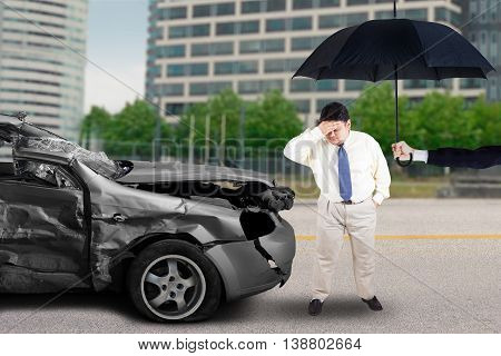 Stressful man standing in front of the broken car under an umbrella after traffic accident on the road. Accident insurance concept