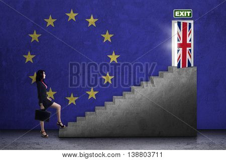 Brexit concept. Young female worker walking on the stairs toward exit door with flag of UK and EU