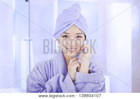 Portrait of beautiful young woman wearing a bathrobe and towel after taking bath on the bathroom