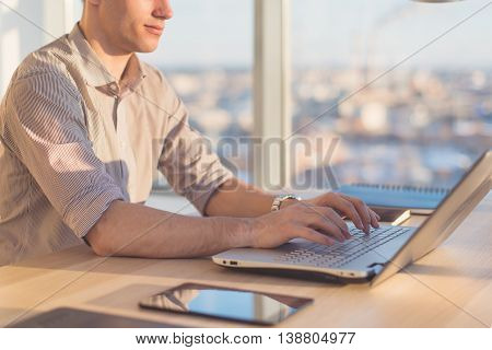 Male hands typing, using laptop in office. Designer working at workplace.