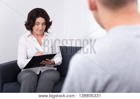 Friendly Female Psychiatrist Working With Her Patient In Office