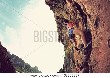 young woman rock climber climbing at seaside mountain cliff