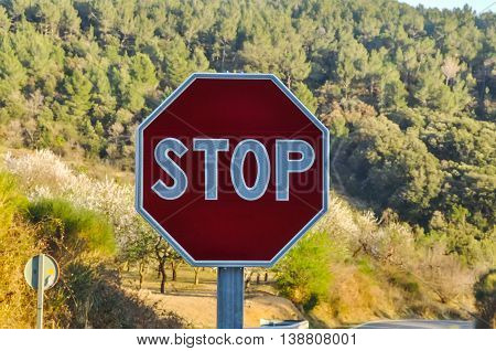 Octagonal stop sign with forested mountain in the background. Horizontal.
